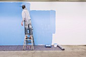 Man standing on ladder painting wall blue