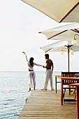Verliebtes Paar am Meer auf einem Holzdeck stehend