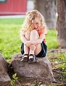 Smiling Caucasian girl sitting on rock