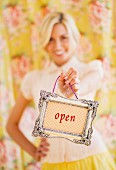 Young woman hold an 'open' sign