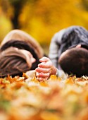 Lovers lying together in an autumnal park