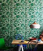 Retro lamp above dining table with Thonet chairs partially dipped in paint against leaf-patterned wallpaper
