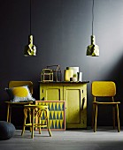 Yellow retro furniture against black wall; vintage-style half-height cabinet between chairs with yellow felt covers