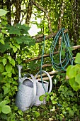 Watering cans and hose in garden