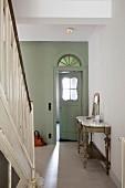 Stilvoll restaurierte Diele mit Holztreppe und Tür zum Windfang mit nostalgischem Türfenster und buntem Rundbogenfenster