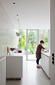 White, designer kitchen with tiled wall and view of garden through open sliding terrace door
