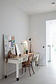 Nostalgic desk with desk lamp, two different chairs and pin board leaning against wall