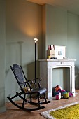 Nostalgic, black wooden rocking chair next to disused, decorated fireplace and illuminated standard lamp