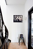 Container on classic metal stool in corner of landing below framed black and white photo on wall