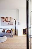 Blick durch offene Tür in minimalistischen Wohnzimmer mit Fischgrät-Parkettboden, neben offenem Kamin graue Polstercouch, an Wand grossformatige Photographie