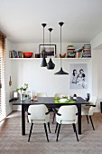 Fifties-style chairs with white leather covers at black dining table below designer pendant lamps and family photo below shelves on wall in background