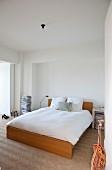 View through open door of double bed with wooden frame on herringbone parquet floor in minimalist bedroom