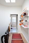 Folkloristische Teppichläufer in Treppenhausflur, seitlich weisse Regalböden an Wand, am Ende des Flurs offene Tür und Blick ins Bad