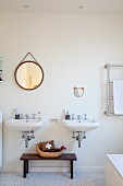 Bowl on simple wooden bench between twin sinks, round mirror on wall and partially visible stainless steel towel rack