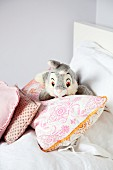 Pale grey rabbit soft toy amongst scatter cushions on bed