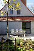 Terrassenplatz vor Anbau eines Wohnhauses an grau verputzter Giebelfassade