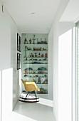 Eames-Schaukelstuhl vor antikem Spielzeug hinter Glastür im hellen Flurbereich