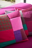 Patchwork-Kisssen in verschiedenen Rottönen und Pastellfarben auf pinkfarbener Polstercouch