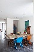 Retro shell chairs in different colours at rustic, wooden kitchen table with frosted glass panel in masonry partition in background