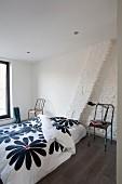 Schlichtes Bett mit geblümter Bettwäsche und Retro-Metallstühlen in minimalistischem Schlafzimmer