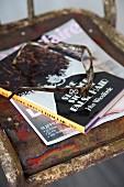 Lesebrille und Buch auf Metallstuhl mit abblätternder Farbe
