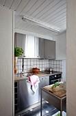 Einblick in Küche mit Edelstahlfronten und gefliestem weißem Spritzschutz, Holzdecke weiß gestrichen