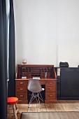 Antiker Sekretär mit grauem Eames Chair in Zimmerecke einer renovierten Altbauwohnung