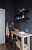Untreated wooden kitchen counter and two dark grey bar stools below black shelves on dark wall