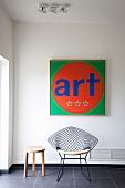Quadratisches modernes farbenfrohes Bild mit Schrift und Wire Chair auf dunklem Fliesenboden