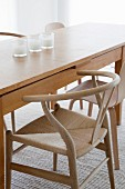 Long, designer wooden table and wooden armchair in Scandinavian style