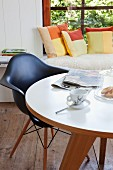 Classic, black armchair at round table in front of window seat with colourful patchwork scatter cushions