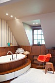 Klassiker Schaukelstuhl in Rot und Hocker aus Holz neben ovaler Badewanne mit Holzverkleidung und umlaufender Stufe im Dachzimmer mit Gaubenfenster