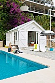 White beach cottage with spacious wooden deck next to the pool with mosaic tiles