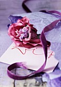 Romantic, pink crocheted flower, wrapping paper, purple velvet ribbon and envelope with writing