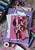 Artistic collection of pictures, notebook, paintbrushes and crocheted flowers tied in bundle with pink velvet ribbon