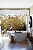 Free-standing bathtub in modern bathroom in front of open terrace door with view into courtyard