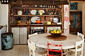 Fruit bowl on round table in front of rustic, vintage kitchen counter with open-fronted shelves