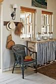 Vintage-Rattanstuhl, Glasbehälter auf Anrichte mit blauweiss gestreiftem Vorhang am Fenster