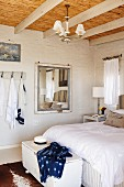 White trunk at foot of double bed with white bed linen in bedroom with wood-beamed ceiling with bamboo covering