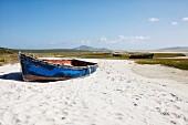 Schlichtes Boot mit blauer, abblätternder Farbe auf Sandplatz am Strand