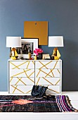 Table lamps with white lampshades and brass bases on white chest of drawers with pattern of gold stripes on drawers against wall painted blue-grey