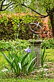 Flowering iris in front of armillary sundial on stone plinth in romantic garden