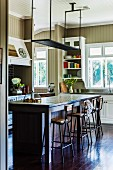 Suspended shelf over breakfast bar with bar stools on dark board floor in wood-clad kitchen with country-house charm painted light brown