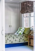 Bed with patterned bedspread and stacked scatter pillows in front of fitted wardrobe in white, wood-panelled bedroom
