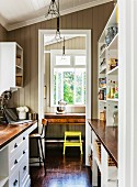 Country-house-style galley kitchen with view of writing desk and yellow stool through doorway