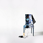 Chair with unusual cover made from patchwork of jeans pockets on the left side and floral patterns on the right