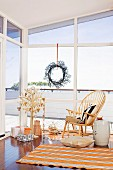 Presents under a stylized Christmas tree and classic chair in front of a window with a decorative wreath