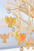 Home-made paper angel figures on a stylized Christmas tree