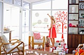Living room with lots of Christmas presents, young woman decorating windows
