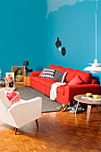 Living room with a feminine touch, blue walls and red sofa